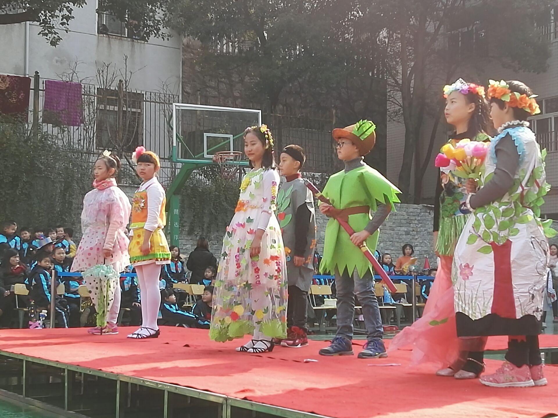 学生通过穿着自己和家长制作的服装在T台上走秀,表明他们对环保理念的